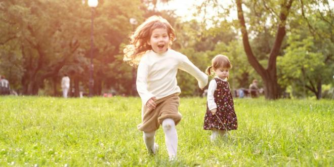 Young girls running and playing in a sunny field